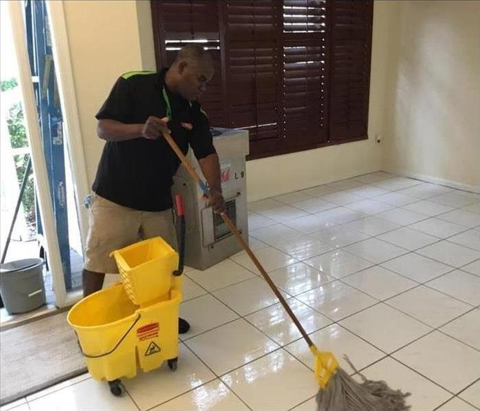 Technician cleaning floor with a mop